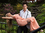Young man holding a fainting young woman in his arms on a bridge springtime nature scenic