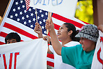 Local advocates wave signs and flags in support of national immigration reform May 1.