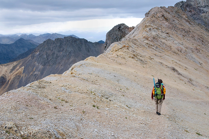 Grizzly Peak awaits as a hiker approaches by a long ridgeline.