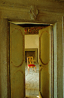 A chair in the piano nobile glimpsed through the partially open doors