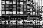 A shinkansen bullet train is reflected in the mirrored glass of a building in Yokohama, Japan