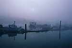 Sunrise La Connor with marinas and downtown along the Swinomish channel in fog with fishing boats moored at dock Washington State USA