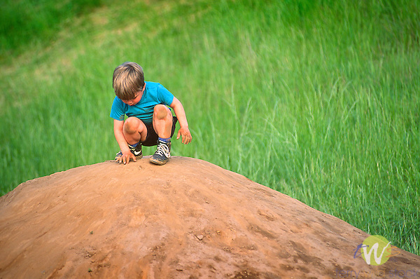 Boy playing on dirt pile hill.