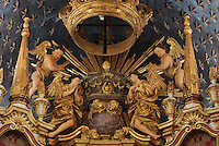 Detail of crown and angels on the stepped Mannerist altarpiece, designed by Bernardo Coelho in 1605 and made by sculptor Simon Mota, with paintings by Simon Rodrigues and Domingos Vieira Serrao, in Sao Miguel Chapel, or St Michael's Chapel, designed in Manueline style 1517-22 by Marco Pires and completed by Diogo de Castilho, on the site of a 12th century chapel in the University of Coimbra, Coimbra, Portugal. The chapel was renovated in the 17th and 18th centuries, with Manuel Ramos making the pulpit in 1684, ceiling painted by Francisco F de Araujo, tiled floor added 1613, Baroque organ with 2,000 pipes built 1733 by Fray Manuel de Sao Bento, and Gabriel Ferreira da Cunha painting chinoiserie elements in 1737. The University of Coimbra was first founded in 1290 and moved to Coimbra in 1308 and to the royal palace in 1537. The building is listed as a historic monument and a UNESCO World Heritage Site. Picture by Manuel Cohen