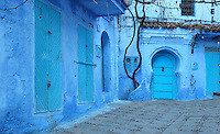 House and shop doors painted blue in a street in the medina or old town of Chefchaouen in the Rif mountains of North West Morocco. The door on the right is studded in the traditional style and recessed in a horseshoe arch niche. Chefchaouen was founded in 1471 by Moulay Ali Ben Moussa Ben Rashid El Alami to house the muslims expelled from Andalusia. It is famous for its blue painted houses, originated by the Jewish community, and is listed by UNESCO under the Intangible Cultural Heritage of Humanity. Picture by Manuel Cohen