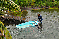 Teahupoo, Tahiti Iti, French Polynesia. Thursday August 24,  2011. Popa Teava salvages one of his boats after a strom. An overnight storm with howling winds and driving rain created conditions which made surfing virtually impossible today.  Photo: joliphotos.com