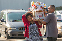 A volunteer helps a woman carry her fresh groceries from a distribution site.Thousands of pounds of food are delivered to a distribution site in Sangar, CA.