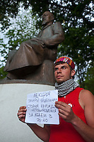 Moscow, Russia, 12/05/2012..A protester under  the statue of Kazakh poet Abai Kunanbaev holds a sign announcing a political lecture in Chistiye Prudy, or Clean Ponds, a park in central Moscow were some 200 opposition activists have set up camp.