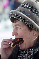 Istra, Russia, 06/03/2011..A woman eats blini, or pancakes, as people celebrate Maslenitsa, also known as Butter Week or Pancake Week. Maslenitsa marks the beginning of the Russian Orthodox period of Lent, but is a traditional Russian Holiday marking the end of winter, and has its origins in pagan times.