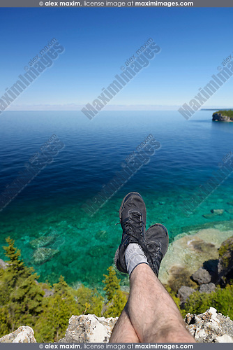 Legs of a person sitting high on a cliff above Georgian Bay, lake Huron at Bruce Peninsula National Park, Ontario, Canada