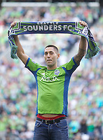 Clint Dempsey holds up a scar after being introduced as a Sounder before a game against the Sounders FC and FC Dallas at CenturyLink Field in Seattle Saturday August, 3, 2013. The Sounders defeated Dallas 3-0.