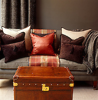 In a London living room an antique leather trunk also serves as a coffee table