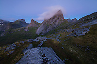 Twilight clouds swirl over dramatic summit of Kråkhammartind mountain peak, Moskenesøy, Lofoten Islands, Norway