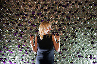 Moscow, Russia, 23/10/2009..A woman poses with a floral display at the Millionaire Fair in Moscow. The event has become an annual fixture, attracting thousands of would-be and existing Russian millionaires to view and purchase a wide range of luxury goods. This year however the fair was much smaller, an indication of how the formerly booming Russian economy has been hit by the world financial crisis.