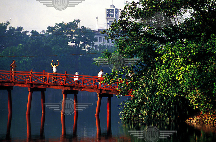 Old men exersizing early in the morning on a bridge over a lake in the centre of Hanoi, Vietnam's capital city.  Credit: Chris Stowers.