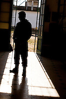 South America, Argentina, La Plata, Los Olmos. Freedom Behind Bars, Prison and Divinity - A guard in the corridor of Unit 25 of Los Olmos Prison. Los Olmos Prison is one of the principal security prisons in Argentina. It hosts Unit 25, known as Christ the Only Hope Prison Church, one of the largest prison churches worldwide. The transformation of criminals into the God fearing and leading them to the Lord has taken hold, not only in the lives of inmates, but also in inmate families and prison guards. Once the countries worst killers and thieves have since become spiritual leaders to other criminals, creating a revolutionary spiritual rehabilitation, July 2006 &copy; Stephen Blake Farrington<br />