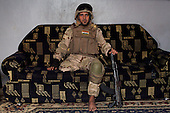 BAGHDAD, IRAQ: Hussein sits on his couch in his army uniform...On January 22nd, 2012, an IED (Improvised Explosive Devise) detonated near an Iraqi Army base in Fallujah. Hussein Jamil Abdullah, a 28 year-old soldier from Baghdad was nearby when the explosive discharged, knocking him to the ground. Hey lay there for half an hour, his right leg in an jerry-rigged tourniquet made from a headscarf, before he was taken to hospital...Gangrene set in almost immediately and the doctors at Fallujah General Hospital had to amputate his leg. He was then moved to Adnan Hospital, the military medical center, but the care Hussein received was terrible. His bandage wasn'.t changed for two days and fearing that gangrene would set in a second time his family moved him to Kerkh Hospital, which they had to cover the costs themselves, as the army refused to pay...As soon as he was wounded, the Army cut Hussein.s salary in half: from $500 a month to $250, which is less than he can live on. His brother, Ali, has given up his work as a barber to take care of him, and his two other brothers, Abbas and Hassan, now take care of the family...Before he was wounded, Hussein, was to be engaged to his fianc&eacute;e, Hind and he had even bought and furnished a room in preparation. But, after the explosion, Hind.'s father refused to allow them to marry, saying that they can.t do so until Hussein gets a prosthetic leg...In the summer, a selection of photographs were published online and caught the attention of an NGO worker in Baghdad who arranged for Hussein to have a prosthetic leg fitted...Once he had his prosthetic leg, Hussein married Hind...Photo by Ali Arkady/Metrography