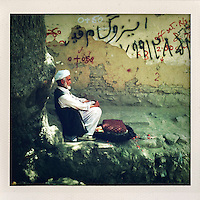A man sits next to a crumbling wall covered in graffiti.