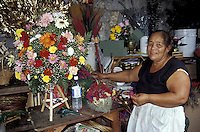 Woman standing next to flower arrangement in the Guamilito Market, San Pedro Sula, Honduras