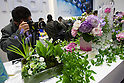 February 9, 2012, Yokohama, Japan - A visitor takes a photo of flowers at the Tamron booth at the CP+ Camera and Photo Imaging Show 2012. The event is held from February 9-12. (Photo by Christopher Jue/AFLO)