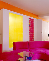 The living area of this apartment is a riot of strong colours