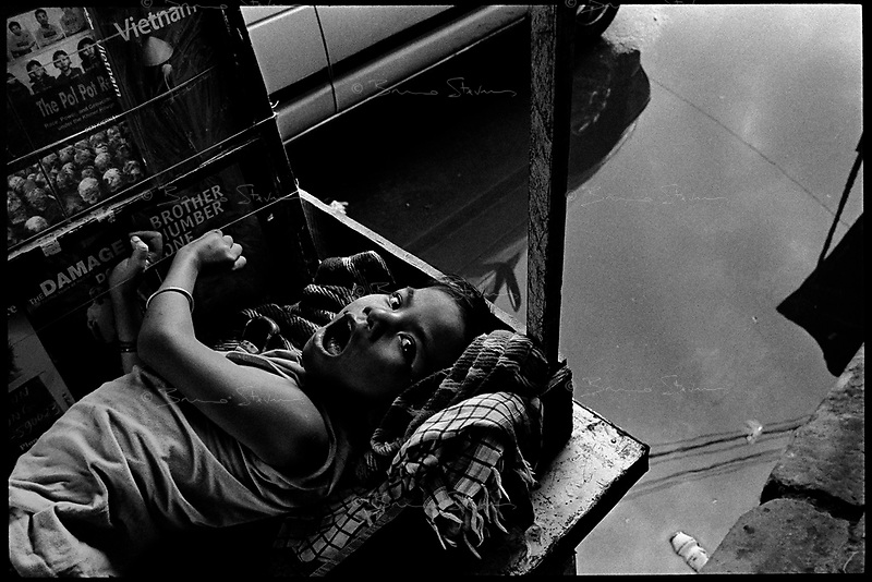 Siem Reap, Cambodia, December 2006..Tro La, 9, suffers from 'spina bifida', a very serious mental and physical condition, usually consecutive to a genetic disorder.  He is completely dependent from his mother selling books to tourists in the market. The abnormally high numbers of similar cases in the whole of Indochina comes as a longterm consequence of the extensive use of 'agent orange' (a dioxine ladden defoliant) by the US Air Force during the Vietnam war.