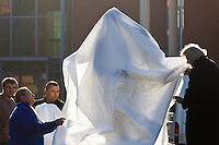 Sculptor Erno Toth (R) covers the first ever life-size bronze statue of late Apple leader Steve Jobs he created with a white textile in its final place in front of the Graphisoft building in Budapest, Hungary on December 13, 2011. ATTILA VOLGYI