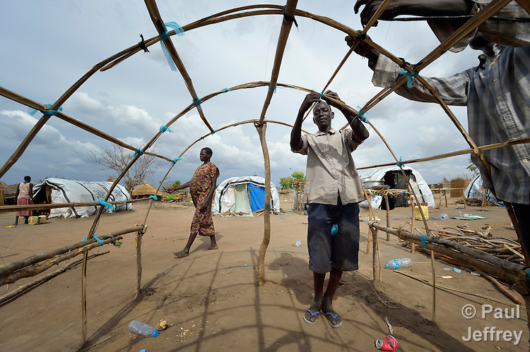 Gumbo Paul builds the framework for his family's tent in a camp for almost 500 internally displaced people located at the St. Vincent de Paul Catholic parish on the edge of Juba, the capital of South Sudan. The families here fled fighting that broke out in December 2013. Paul, along with his wife and five children, came to Juba from Bentieu. More than 700,000 people have been internally displaced in the first three months.