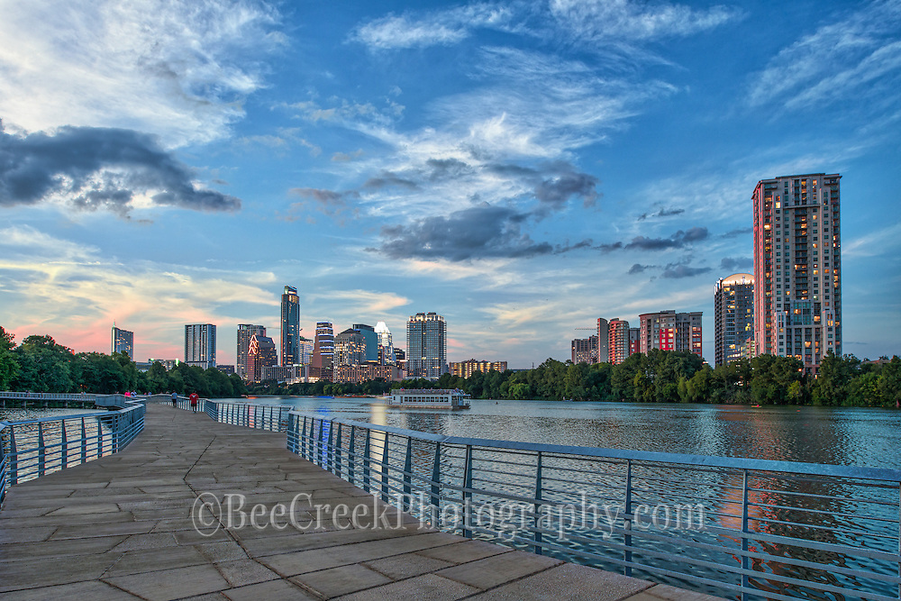 """This is an image of the Austin boardwalk at dusk with one of the toursit boats on Ladybird Lake taking in the sunset. Austin is home to the State Capital with a beautiful skyline along Ladybird Lake.  There are many new high rises buildings in the downtown area of the city which can be seen from the boardwalk hike and bike trail as seen in this photo.  Austin Texas is the capital of Texas and the city is growing at leaps and bounds many of these downtown high rises skyscrapers were not here ten years ago most have gone up in the last five years. In this photo we capture beautiful fall colors on  this December day with the tree displaying colors from the hike and bike trail with one of the paddle boat on the water full of tourist enjoying a nice day on Ladybird Lake and a lovely city view. The skyline of Austin is always changing and the downtown area has many new residences who live in the city so it is a very active place with many restaurants, several parks, hike and bike trails, the warehouse district night life and of course six street where the term """"Live Music Capital"""" came from. Sometimes living in Austin for locals can be difficult, because there is always something going on so a lazy walk down the trails may turn in to a fight for a parking space, but for those that live in the city it just a heart beat away."""