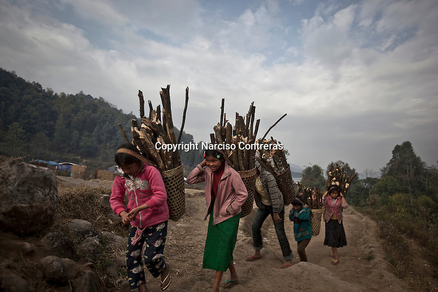Kachin refugees carry firewood collected foreground to Je Gau Pa IDP camp located at the high mountains of northeastern Kachin State. The camp gives shelter to two thousand displaced persons from the war-torn villages close to Maiya Jang city. The KIA positions around the city have been attacked by shelling and heavy artillery during months. Fierce clashes have taken place since the ceasefire was broken out by the Burmese army last June 2011. During months the fighting were spread out along the Kachin State leaving more than 40,000 displaced persons and refugees (a conservative estimating) in accord with the humanitarian aid groups.