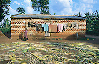 Uganda. Kayunga district. Nnongo. A farmer house, which is made with red bricks, stands in the middle of the fields. A woman  and her washed clothes drying in the sun. Palm tree branches are laid on the ground. .© 2004 Didier Ruef