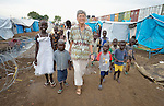 Sister Cathy Arata, a School Sister of Notre Dame from New Jersey, walks with children in a camp for internally displaced families located inside a United Nations base in Juba, South Sudan. The camp holds Nuer families who took refuge there in December 2013 after a political dispute within the country's ruling party quickly fractured the young nation along ethnic and tribal lines. Arata provides assistance to pastoral groups as a member of Solidarity with South Sudan, an international network of Catholic congregations assisting with pastoral work and the training of health workers and teachers.
