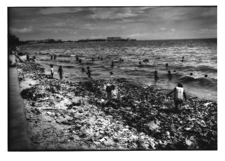 Squatters picking through rubbish washed up along Roxas Blvd. baywalk while people bathe nearby, Manila Bay, Philippines.
