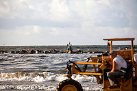 A cleanup worker uses a tractor to collect contaminated soil on the coast of Grand Isle, LA  on June 23, 2010 where oil has reached the shore. The Deepwater Horizon and the British Petroleum oil spill has been claimed as the most damaging environmental disaster in history.
