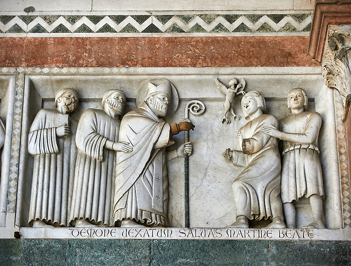 Late medieval relief sculpture of St Martin expelling an evil demon from a robber on the Facade of the Cattedrale di San Martino,  Duomo of Lucca, Tunscany, Italy,
