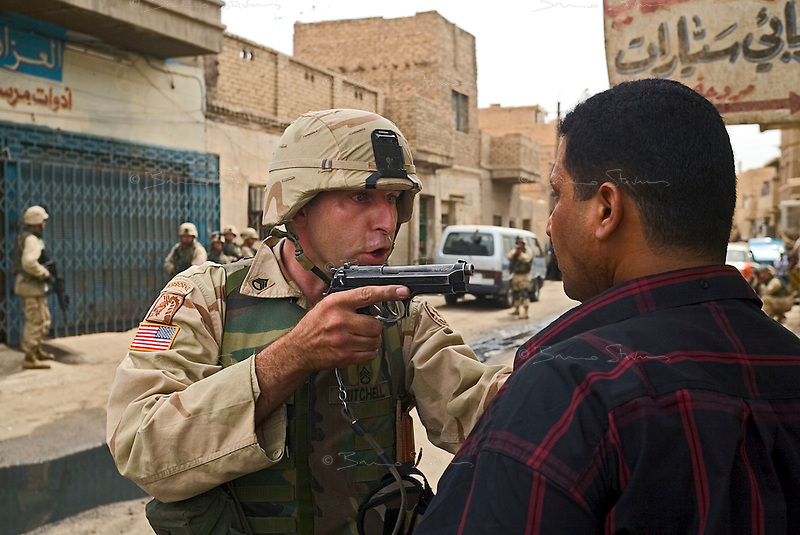 """Baghdad, Iraq, June 2, 2003.US troops often completely misunderstand perfectly benign circumstances for lack of translators and proper training, creating potentially dangerous situations for the Iraqi population they are supposed to protect. Here, a couple of gunshots were fired in the air at the end of a wedding as is customary, US troops patrolling the area blocked up a street and tried to break into a house where they wrongly thought the """"shooter"""" had taken refuge, the man being arrested and quite brutally treated, is in fact the owner of the house who keenly offered to open it to prove it was empty..."""