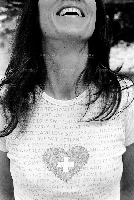 Switzerland. Canton Ticino. Lugano. Woman standing outside laughing and wearing a T-shirt with a heart, the swiss flag and the words which say: Switzerland Love. © 2007 Didier Ruef