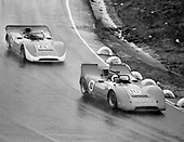 Chuck Parsons (no. 10) leads Skip Scott in the Haas Lola T160s through the rain in the 1968 Laguna Seca Can-Am.