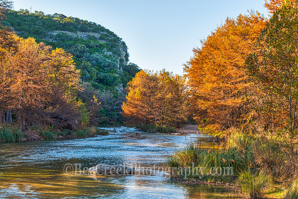 Con Can on the Frio River on a fall day as the sun is low in the sky.  You can see the cool clear waters as they flow down stream with the oranges, reds, color in the cypress trees that are along the rivers edge.