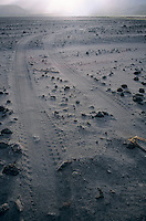 Tyre tracks and lava rocks on the vast ash plain near Mount Yasur, and active volcano on the island of Tanna, Vanuatu.