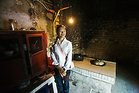 Young Chinese woman shows an old kitchen of an ancient house, nearby Yangshuo town.