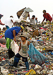 Children working in the municipal dump in Manila, the capital of the Philippines. Children and their parents work day and night in the dump, scavenging for items of value, including plastic, glass and metal, that can be recycled..