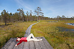 Young Woman Lying on Wooden Boardwalk by Viru Bog Pool, Lääne-Viru County, Estonia