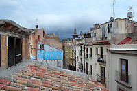 Rooftops of houses along a narrow street, including Casa Grego, in the old town or Casc Antic and the octagonal stained glass skylight and iron belfry of the Church of Reparacion, built 1899 by Joan Abril i Guanyabens, Tortosa, Tarragona, Spain. Tortosa is an ancient town situated on the Ebro Delta which has a rich heritage dating from Roman times. In recent years, many buildings in the old town have been abandoned and fallen into disrepair. Picture by Manuel Cohen