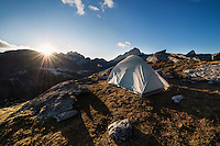 Tent and setting sun in mountain campsite, Moskenesøy, Lofoten Islands, Norway