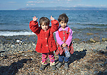 Two refugee girls stand on a beach near Molyvos, on the Greek island of Lesbos, on October 29, 2015, after they and their family crossed the Aegean Sea from Turkey in a small overcrowded boat provided by Turkish traffickers to whom the refugees paid huge sums. They were received in Greece by local and international volunteers, then proceeded on their way toward western Europe.