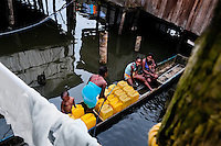 A Colombian woman fills plastic barrels with safe drinking water inside the stilt house area in Tumaco, Colombia, 17 June 2010. Although Latin America (as a whole) is blessed with an abundance of fresh water, having 20% of global water resources in the the Amazon Basin and the highest annual rainfall of any region in the world, an estimated 50-70 million Latin Americans (one-tenth of the continent's population) lack access to safe water and 100 million people have no access to any safe sanitation. Complicated geographical conditions (mainly on the Pacific coast), unregulated industrialization (causing environmental pollution) and massive urban poverty, combined with deep social inequality, have caused a severe water supply shortage in many Latin American regions.