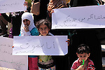 Palestinian relatives of cancer patients hold placards during a protest demanding for the opening of Rafah crossing border, in Gaza City on June 30, 2014. Photo by Ashraf Amra