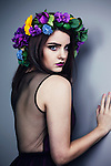 young woman with short dark hair wearing a flower crown looking shy