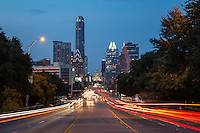 The Austin Skyline and Texas Capitol at dusk as seen from South Congress Avenue looking down across the Congress Avenue Bridge as moving cars leave light trails as they speed along - Stock Image.